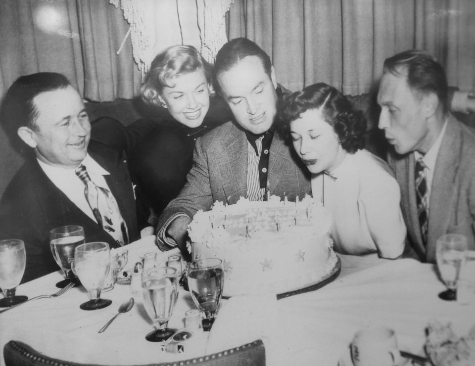 Photo - This framed photograph shows famed comedian and actor Bob Hope, center, blowing out candles on a cake during a birthday party at one of Beverly Osborne's restaurants.  Jim Beckel -  THE OKLAHOMAN