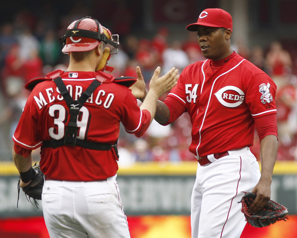 Photo - Cincinnati Reds relief pitcher Aroldis Chapman (54) is congratulated by catcher Devin Mesoraco (39) after the Reds defeated the Philadelphia Phillies 4-1 in a baseball game, Sunday, June 8, 2014, in Cincinnati. (AP Photo/David Kohl)