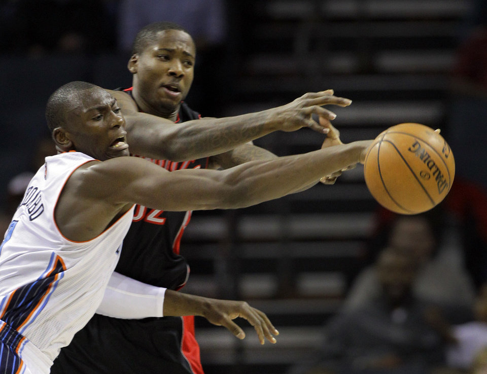 Photo -   Charlotte Bobcats' Bismack Biyombo, front, and Toronto Raptors' Ed Davis, back, reach for a rebound during the first half of an NBA basketball game in Charlotte, N.C., Wednesday, Nov. 21, 2012. (AP Photo/Chuck Burton)