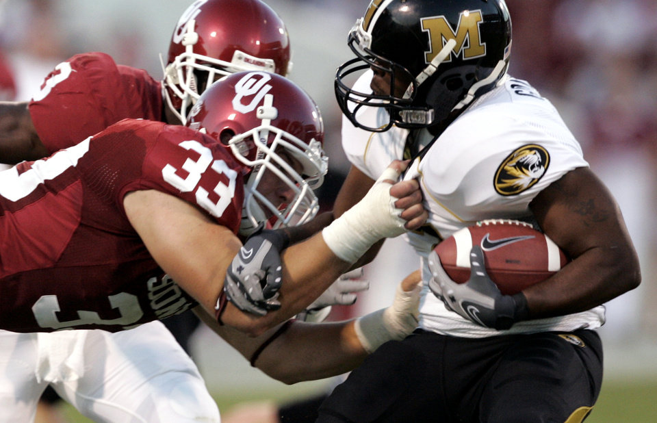 Photo - Oklahoma's Auston English (33) brings down Missouri's Earl Goldsmith (7) during the first half of the college football game between  the University of Oklahoma Sooners (OU) and the University of Missouri Tigers (MU) at the Gaylord Family Oklahoma Memorial Stadium on Saturday, Oct. 13, 2007, in Norman, Okla. By STEVE GOOCH, The Oklahoman