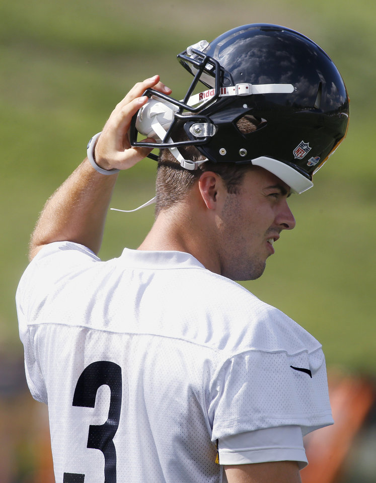 Former Sooner quarterback Landry Jones turns his helmet around during a Pittsburgh Steelers practice in Latrobe, Pa., on Sunday, July 28, 2013. (AP Photo/Keith Srakocic)