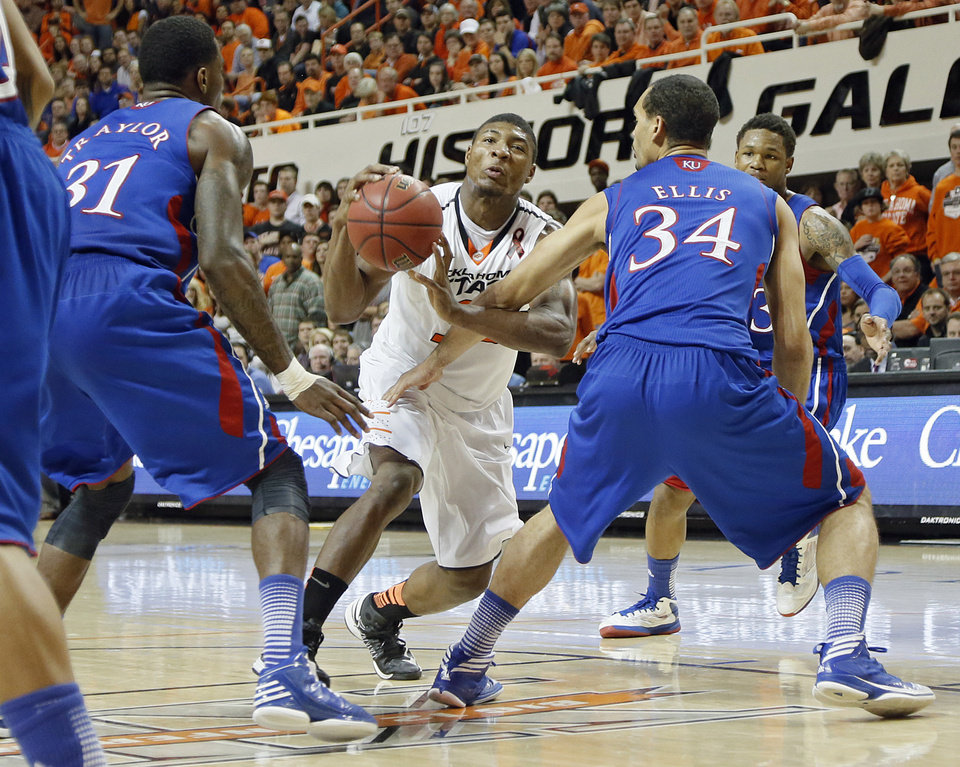 Oklahoma State 's Marcus Smart (33) drives past Kansas' Jamari Traylor (31) and Perry Ellis (34) during the college basketball game between the Oklahoma State University Cowboys (OSU) and the University of Kanas Jayhawks (KU) at Gallagher-Iba Arena on Wednesday, Feb. 20, 2013, in Stillwater, Okla. Photo by Chris Landsberger, The Oklahoman