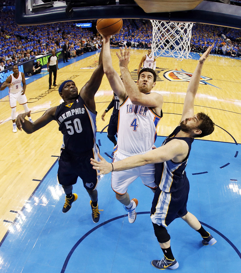 Photo - Oklahoma City's Nick Collison (4) shoots between Memphis' Zach Randolph (50) and Marc Gasol (33) during Game 1 in the first round of the NBA playoffs between the Oklahoma City Thunder and the Memphis Grizzlies at Chesapeake Energy Arena in Oklahoma City, Saturday, April 19, 2014. Photo by Nate Billings, The Oklahoman