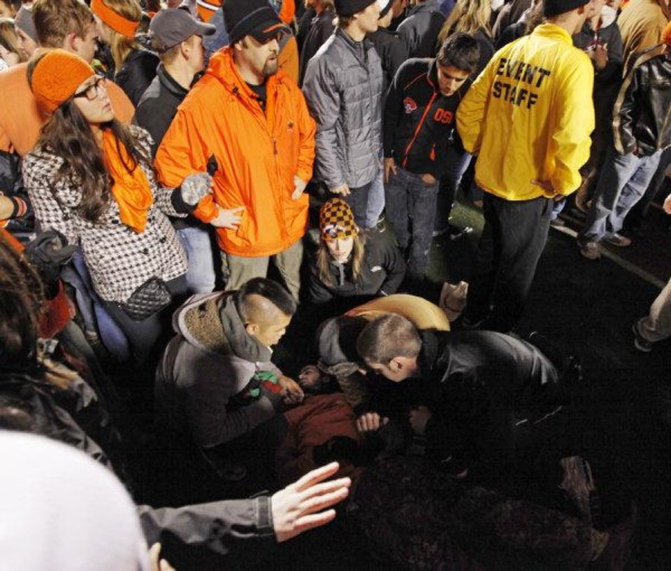 OSU fans and workers keep people away from a fan who was injured when fans stormed the field after the Bedlam college football game between the Oklahoma State University Cowboys and the University of Oklahoma Sooners at Boone Pickens Stadium in Stillwater Saturday. <strong>NATE BILLINGS - NATE BILLINGS</strong>