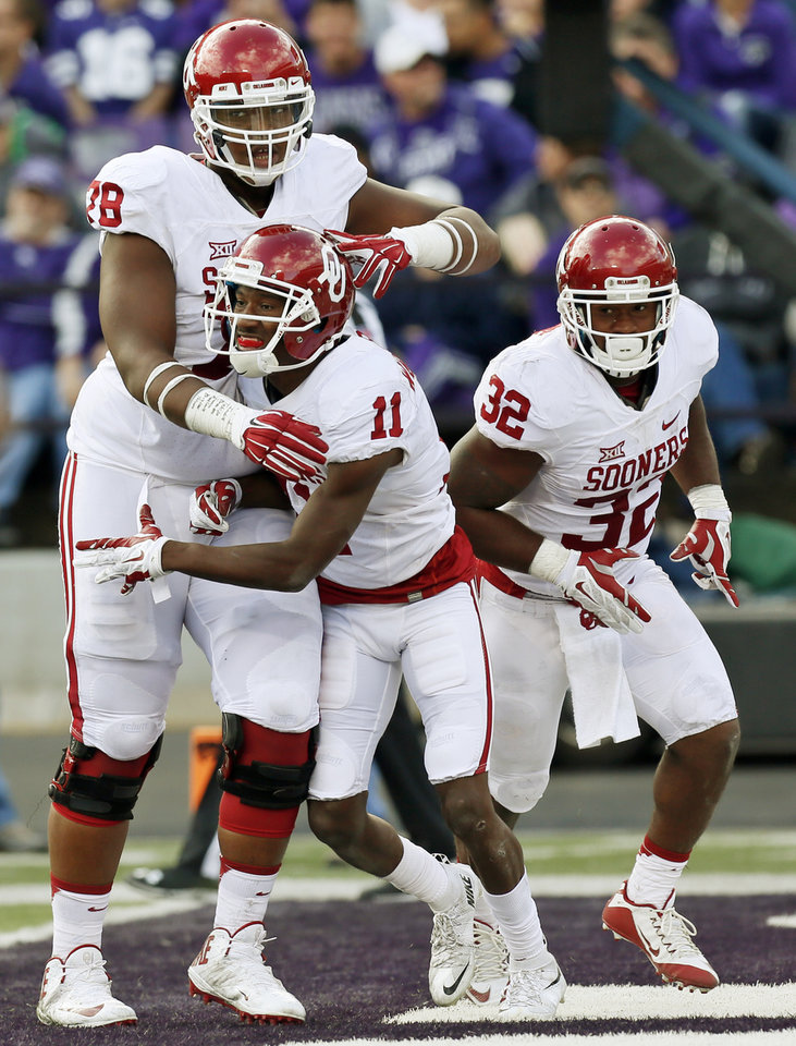 Photo - Oklahoma offensive lineman  Orlando Brown, left, towers over wide receiver Dede Westbrook (11) and running back Samaje Perine (32). (Photo by Nate Billings, The Oklahoman)