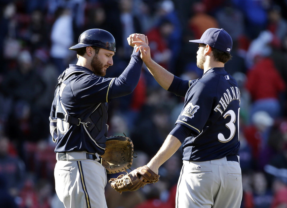 Photo - Milwaukee Brewers catcher Jonathan Lucroy, left, and relief pitcher Tyler Thornburg, right, celebrate after shutting out the Boston Red Sox 4-0 in a baseball game Sunday, April 6, 2014, in Boston. (AP Photo/Steven Senne)