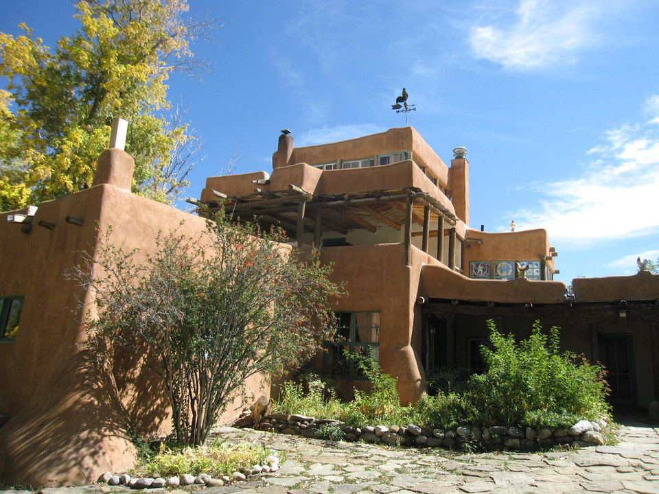 Photo - This Oct. 3, 2012 photo shows the Mabel Dodge Luhan house in Taos, N.M., a historic inn and conference center. Luhan moved to Taos in 1919 and is considered the unofficial founder of the town's artistic and intellectual community. She hosted luminaries like painter Georgia O'Keeffe and photographer Ansel Adams, and D. H. Lawrence painted the home's bathroom windows, which can be seen on an upper floor from the outside. Visitors can stop by the building and grounds, one of a number of attractions in the Taos area. (AP Photo/Beth J. Harpaz)