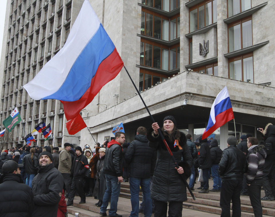 Photo - Pro-Russian activists wave Russian flags at a rally in front of the City Hall in Donetsk, Ukraine, Sunday, March 2, 2014. Ukraine's new prime minister urged Russian President Vladimir Putin to pull back his military Sunday in the conflict between the two countries, warning that
