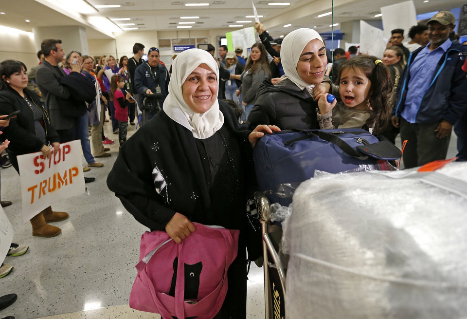 Photo - Najah Alshamieh, left, from Syria, leaves Terminal D of Dallas Fort Worth International Airport in Dallas, after being held inside and later released, Saturday, Jan. 28, 2017. With her is her daughter Mariam Yasin, second from right. Protestors at the airport demonstrated against President Donald Trump's executive order banning individuals from certain Muslim-majority countries from entering the U.S. (Jae S. Lee/The Dallas Morning News via AP)