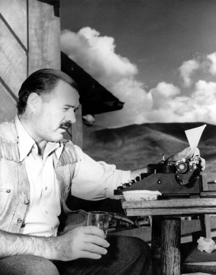 Photo - In this 1939 file photo, American novelist and short-story writer Ernest Hemingway is shown at his typewriter as he works at Sun Valley lodge, Idaho. In