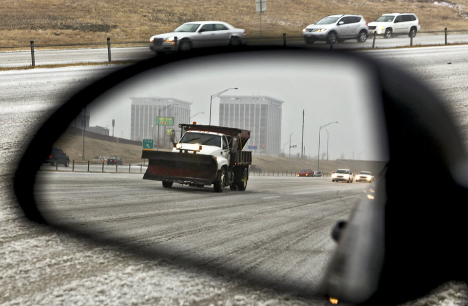 A sand truck reflects in a mirror as it covers the Lake Hefner Parkway as morning traffic navigates its way on icy roads on Thursday Dec. 24, 2009, in Oklahoma City, Okla.   Photo by Chris Landsberger, The Oklahoman