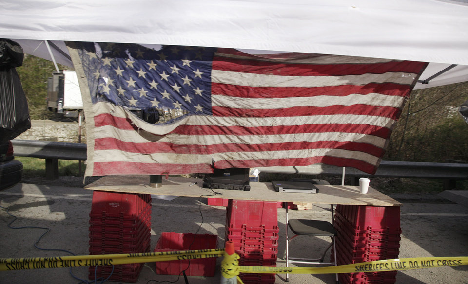 Photo - A tattered flag, found in the debris of a deadly mudslide, is flown at a staging area for emergency workers on Highway 530 near the debris field, Wednesday, April 2, 2014, in Oso, Wash. Officials have so far confirmed the deaths of 29 people, although only 22 have been officially identified in information released Wednesday morning by the Snohomish County medical examiner's office. (AP Photo/Elaine Thompson)