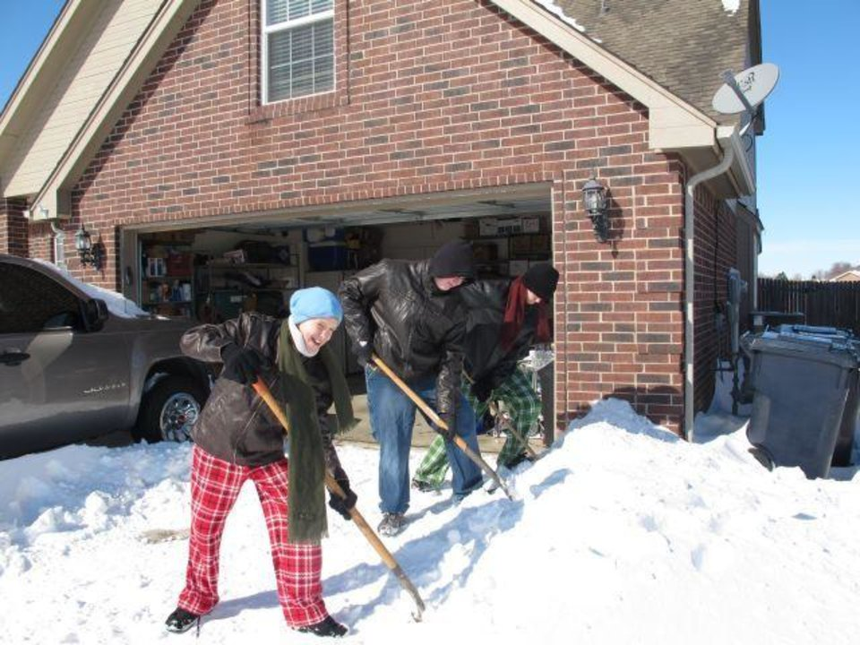 Photo - From left, Nick Liszeski, Colton Box and Stephen Liszeski, all First-Class Boy Scouts in Troop 300 in Yukon, shovel snow Wednesday from a neighbor's driveway. (Photo Provided)
