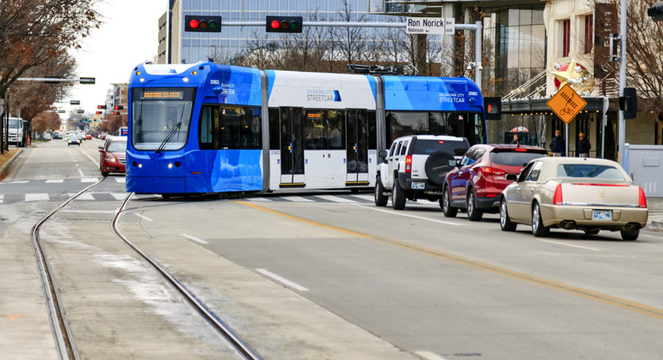Photo - The streetcar makes its way through an intersection on its way to the Century Center stop to pick up passengers during the grand opening celebration day of the Oklahoma City streetcar system in downtown Oklahoma City, Okla. on Friday, Dec. 14, 2018. Photo by Chris Landsberger, The Oklahoman
