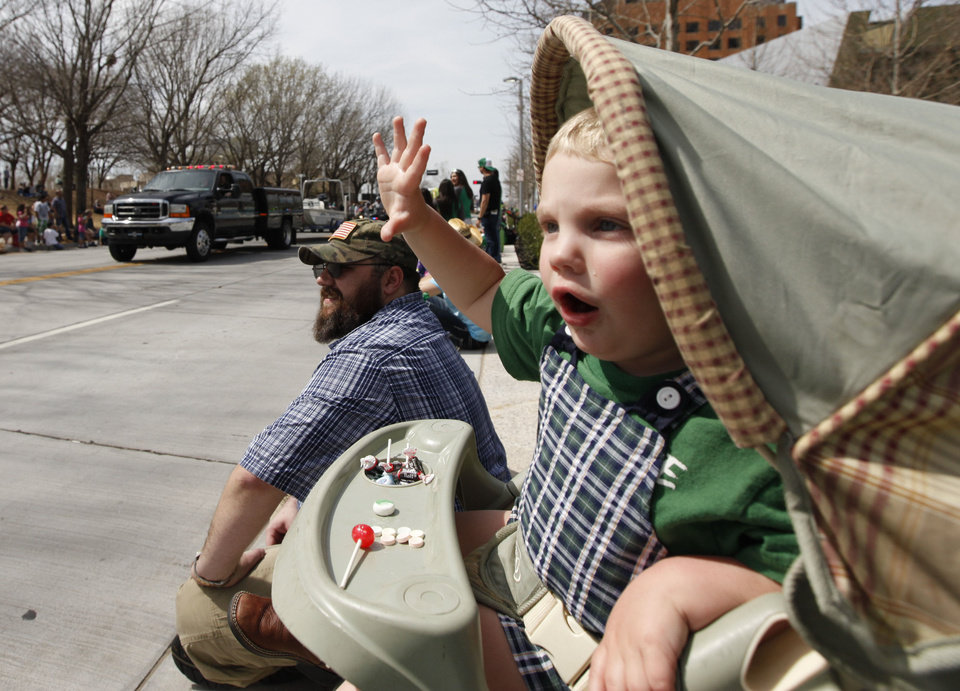 Two-year-old Seamus Carter waves from his stroller Saturday during the annual St. Patrick�s Day Parade in downtown Oklahoma City.  Photos By Paul Hellstern, The Oklahoman