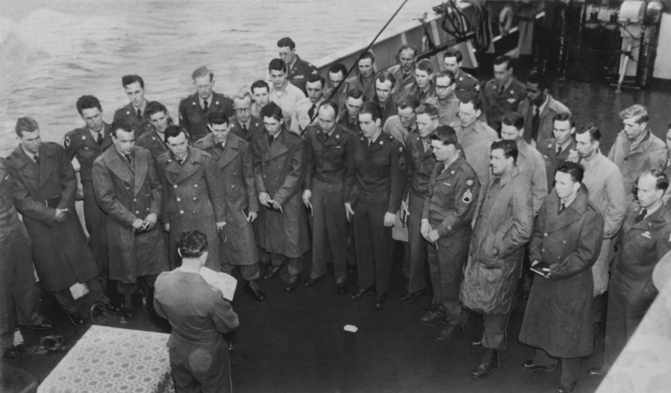 """Photo - Early Sunday morning, before the troop transport Sylvester Antolak docked in Seattle with the first Thunderbirds to return from the Korean battlefront, Easter services were conducted on the deck by Capt. Floyd Merrill of Stillwater.""""  AP Wirephoto, photographer and original date unknown.  Published in The Daily Oklahoman 04/14/1952."""