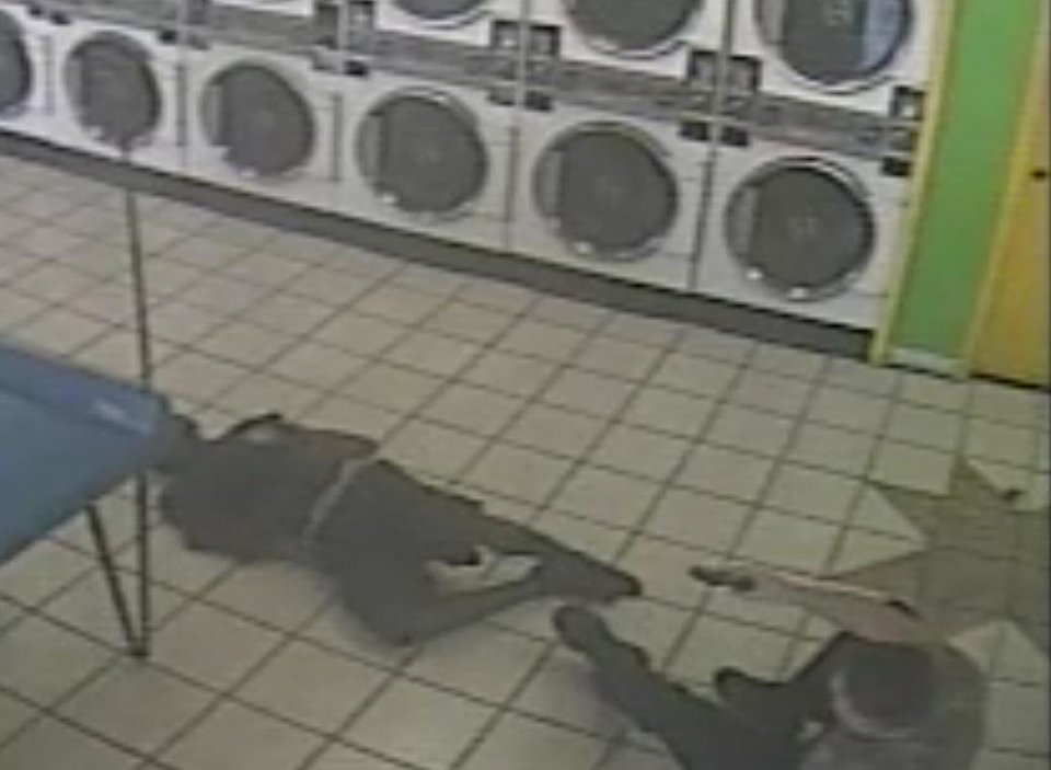 Photo -  A screen shot from surveillance video of a police shooting inside an Oklahoma City laundromat on June 12, 2014. The shooting left Marquis Pegues, now 31, of Oklahoma City, paraplegic.