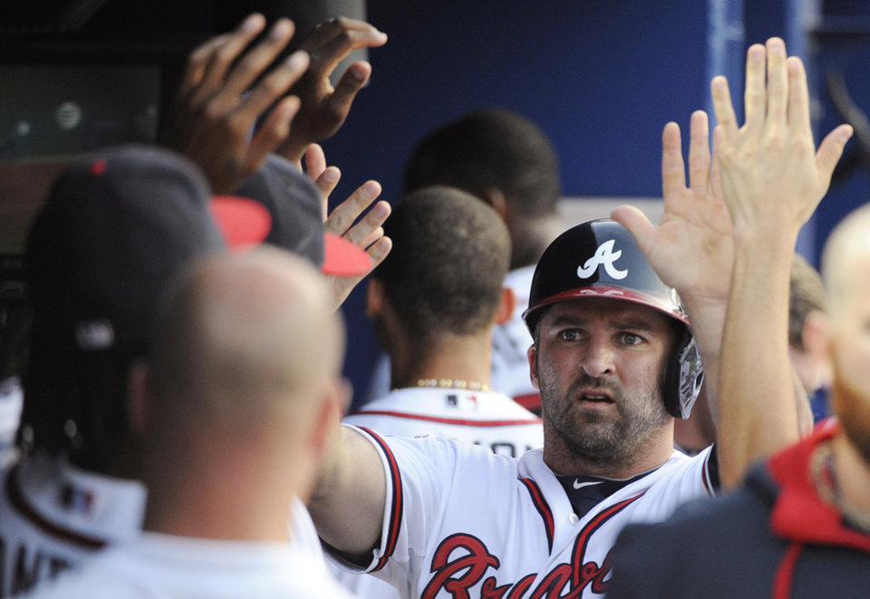 Photo - Atlanta Braves' Dan Uggla is greeted in the dugout after he scores on a double by Gerald Laird during the second inning of a baseball game against the Colorado Rockies on Friday, May 23, 2014, in Atlanta. (AP Photo/David Tulis)