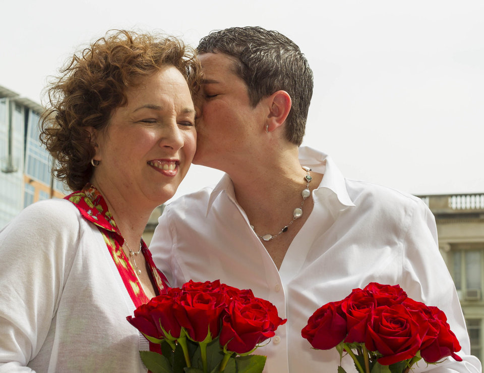 Photo - Kerry Lehman, right, kisses Sara Hinkel, after getting married Saturday, June 7, 2014, in Madison, Wis. The partners, both of Madison, have been together for 14 years. On Friday a federal judge struck down the state's gay marriage ban. (AP Photo/Andy Manis)