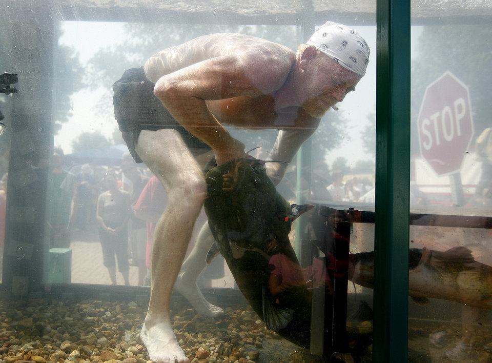 Lee McFarlin of Stillwater, demonstrates noodling during the Okie Noodling Tournament in Pauls Valley on Saturday. (Photo by Bryan Terry, The Oklahoman)