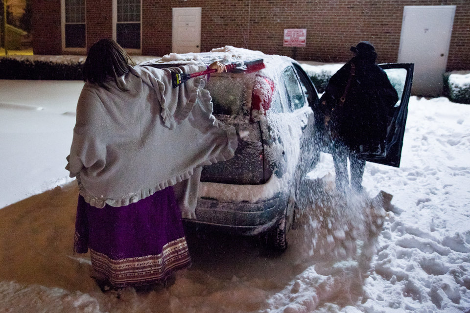 Crystal Thomas scrapes snow off her car following the celebration on the first night of Kwanzaa at Bethel United Methodist Church on Wednesday, Dec. 26, 2012 in Flint, Mich. (AP Photo/The Flint Journal, Griffin Moores) LOCAL TV OUT; LOCAL INTERNET OUT