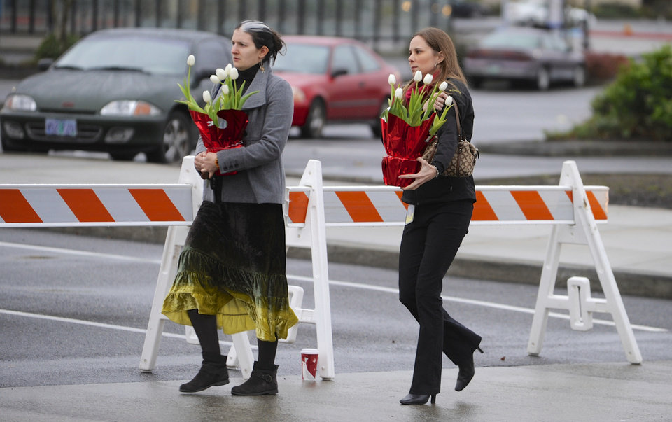 Leslie King, left, and Tenille Beseda carry flowers Wednesday Dec. 12, 2012, to place at the entrance to the scene of a multiple shooting Tuesday at Clackamas Town Center Mall in Portland, Ore. A gunman who opened fire on shoppers at a Portland mall had no connection to the two people he fatally shot and wanted to kill as many people as possible, police said Wednesday.   (AP Photo/Greg Wahl-Stephens)  ORG XMIT: ORGW102
