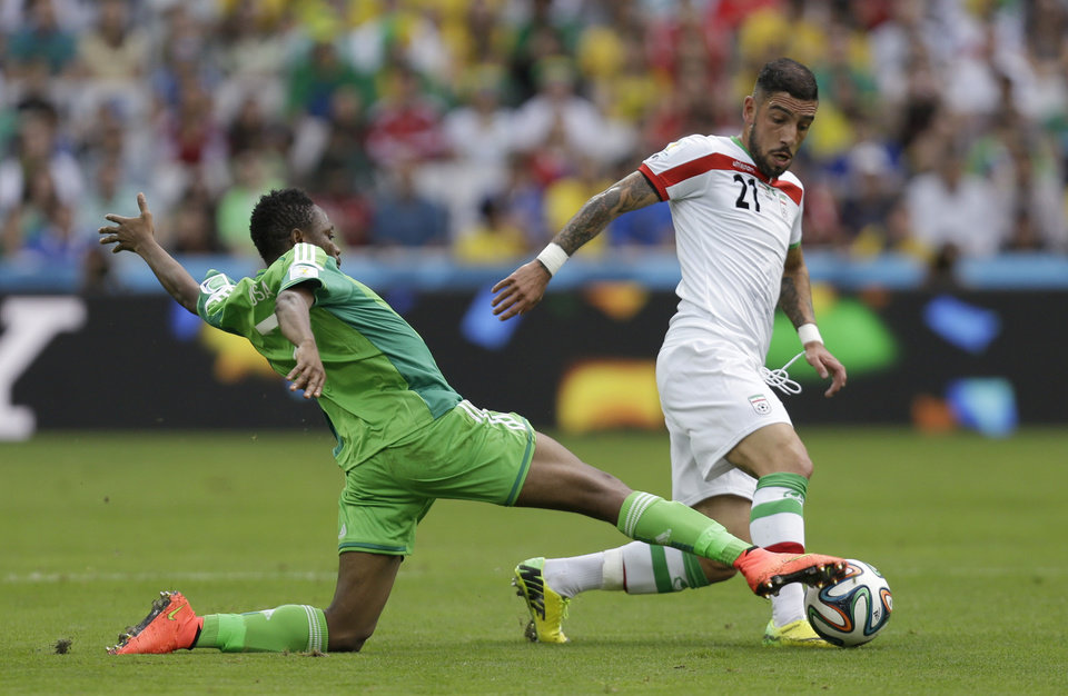 Photo - Nigeria's Ahmed Musa, left, challenges Iran's Ashkan Dejagah during the group F World Cup soccer match between Iran and Nigeria at the Arena da Baixada in Curitiba, Brazil, Monday, June 16, 2014.  (AP Photo/Fernando Vergara)