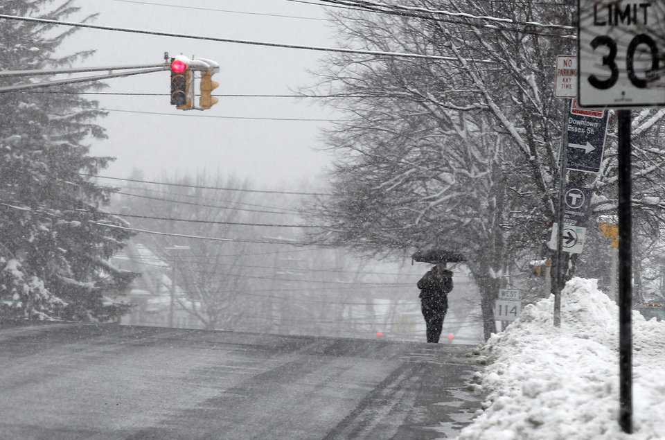 A pedestrian walks down a deserted street during a winter storm in Lawrence, Mass. Tuesday, March 19, 2013. Winter went out with a blast in the Northeast on Tuesday, snow and sleet closing schools in some areas and making roads an icy, slippery mess a day before spring starts. (AP Photo/Winslow Townson)