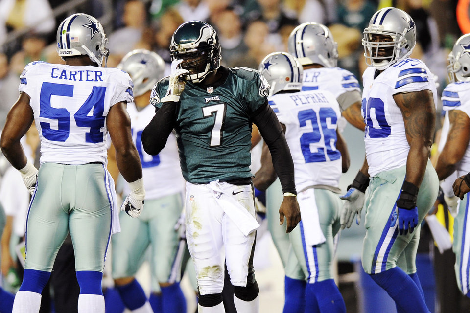 Philadelphia Eagles quarterback Michael Vick (7) adjusts his helmet after being tackled in the first half of an NFL football game against the Dallas Cowboys, Sunday, Nov. 11, 2012, in Philadelphia. (AP Photo/Michael Perez)