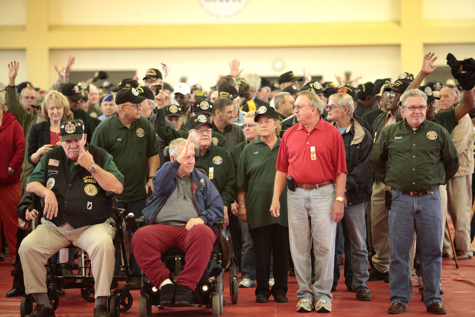 Vietnam veterans wave as they walk into the Rinehart Fitness Center at Fort Sill to a standing ovation for a welcoming home  ceremony, Friday, March 29, 2013. Photo By David McDaniel, The Oklahoman <strong>David McDaniel - The Oklahoman</strong>