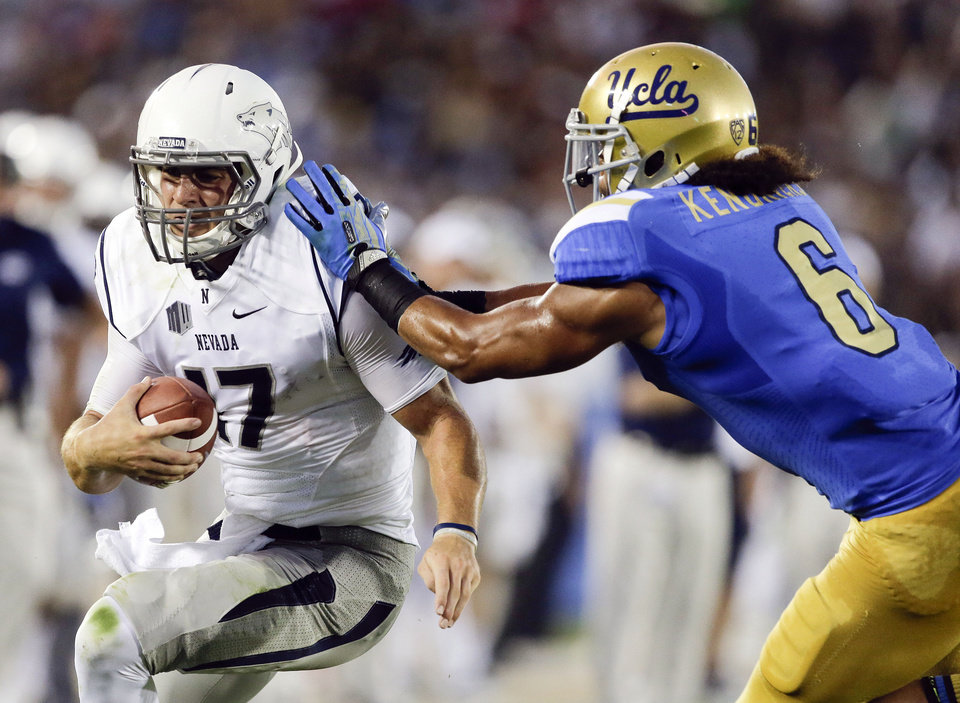 UCLA's Eric Kendricks, right, pushes Nevada quarterback Cody Fajardo out of bounds during the first half of an NCAA college football game in Pasadena, Calif., Saturday, Aug. 31, 2013. (AP Photo/Chris Carlson)