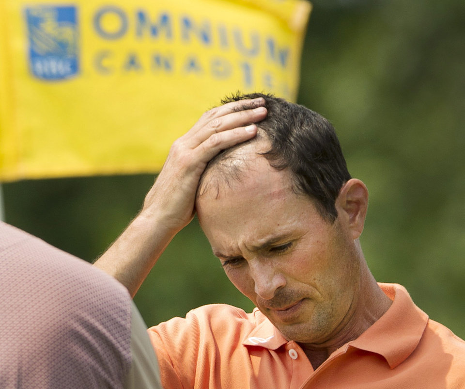 Photo - Canada's Mike Weir walks off the last hole after finishing the second round at the Canadian Open golf championship Friday, July 25, 2014 in Montreal. (AP Photo/The Canadian Press, Ryan Remiorz)