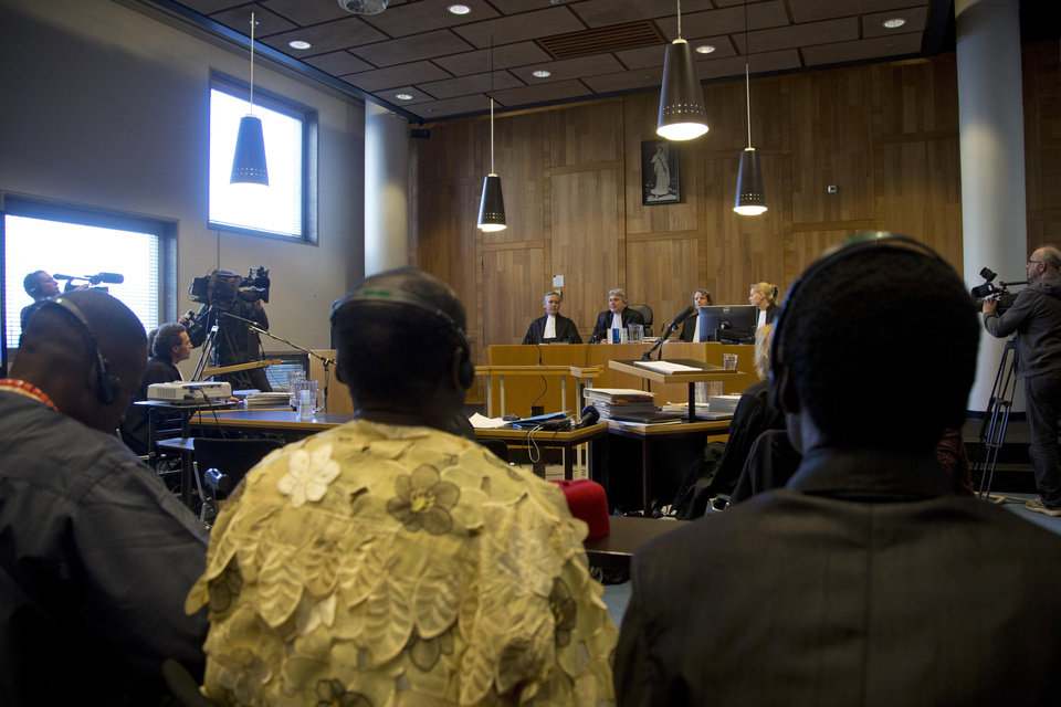 Judges, rear, and Nigerian plaintiffs, front, wait for the start of the court case of Nigerian farmers against Shell in The Hague, Netherlands, Thursday Oct. 11, 2012. Nigerian farmers are suing Shell in a Dutch court, asking judges to order the oil multinational to clean up environmental damage the farmers say is caused by leaking pipes. Thursday's case in The Hague Civil Court is a legal landmark in the Netherlands as it marks the first time a Dutch company has been sued for alleged environmental mismanagement caused by an overseas subsidiary. (AP Photo/Peter Dejong)