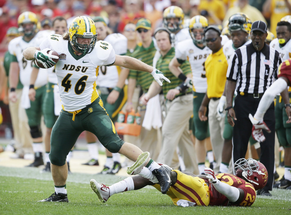 Photo - North Dakota State fullback Andrew Bonnet (46) breaks a tackle by Iowa State defensive back T.J. Mutcherson, right, during the second half of an NCAA college football game, Saturday, Aug. 30, 2014, in Ames, Iowa. North Dakota State won 34-14. (AP Photo/Charlie Neibergall)