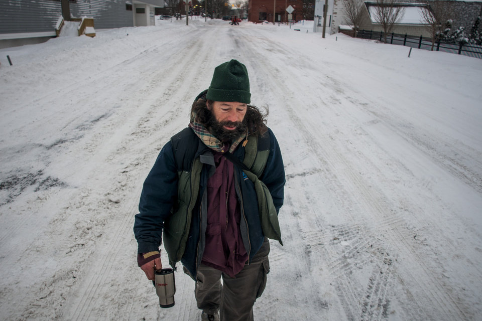 Photo - Homeless man Russell Krisher, 45, walks the streets with a coffee cup in hand and his head down as the wind begins to pick up while walking down the middle of Harrison Street on Monday morning, Jan. 6, 2014, in downtown Flint, Mich., after a severe snowstorm dumped 16.2 inches of snow over the weekend
