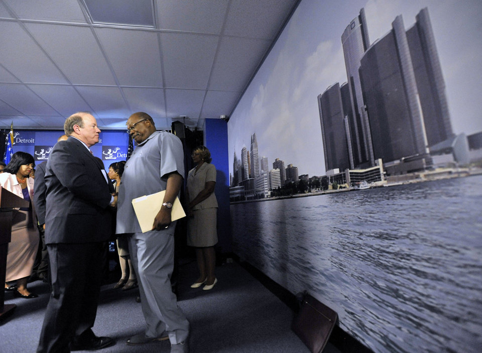 Photo - Detroit Mayor Mike Duggan, left, shakes hands with the Rev. Dr. Wendell Anthony, right, president of the Detroit Branch NAACP, after a news conference on Thursday, Aug. 7, 2014 in Detroit. Duggan announced the city will offer affordable payment plans to many delinquent customers. Detroit shut off water service to around 17,000 to 18,000 residential customers, about 10 percent of the roughly 170,000 total. About 60 percent to 70 percent have been restored, and officials said restorations continue. Shutoffs have been halted until Aug. 25. (AP Photo/Detroit News, Todd McInturf)  DETROIT FREE PRESS OUT; HUFFINGTON POST OUT