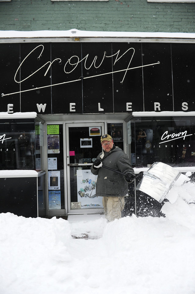 Photo - Bryan Demory shovels the walk in front of Crown Jewelers after a snowstorm accumulating over a foot of snow on Thursday, Feb. 13, 2014, in Staunton, Va. (AP Photo/The News Leader, Katie Currid)