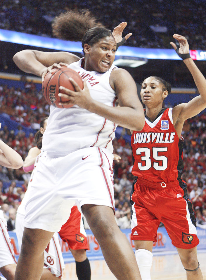 Photo - Courtney Paris pulls in a rebound in front of Louisville's Angel McCoughtry during OU's 61-59 loss Sunday at the Scottrade Center in St. Louis. OU jumped out to an early 11-0 lead, but Louisville fought back and won to advance to the finals. Photo by Steve Sisney, The Oklahoman