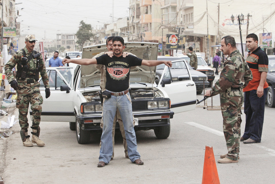 Photo - Sunni paramilitary members search a man at a vehicle checkpoint Monday in the Azamiyah area of north Baghdad. AP PHOTO