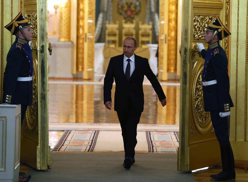 Photo - Russian President Vladimir Putin enters the hall to address the Federal Assembly in the Kremlin in Moscow,  Tuesday, March 18, 2014. President Vladimir Putin on Tuesday signed a treaty to incorporate Crimea into Russia, describing the move as the restoration of historic injustice and a necessary response to what he called the Western encroachment on Russia's vital interests.  (AP Photo/Sergei Ilnitsky, pool)