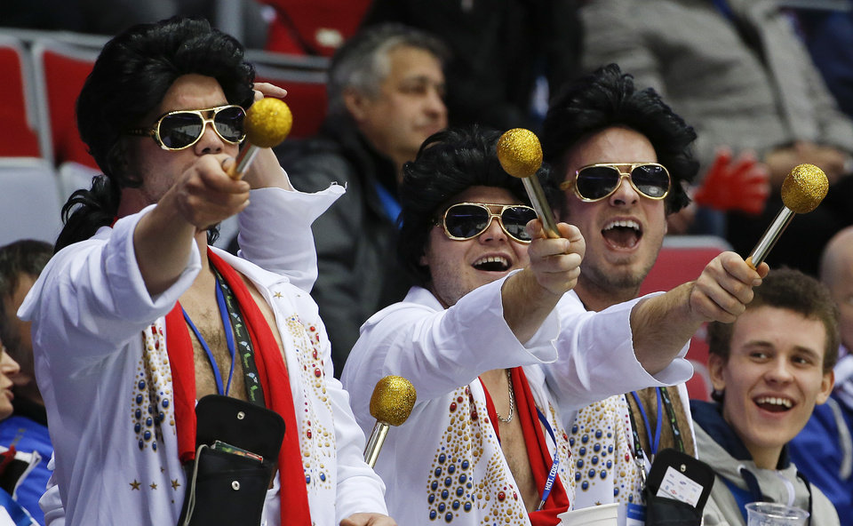 Photo - Hockey fans dressed as Elvis entertain other fans during a break in play during the third period of a men's quarterfinal ice hockey game between Canada and Latvia at the 2014 Winter Olympics, Wednesday, Feb. 19, 2014, in Sochi, Russia. (AP Photo/Julio Cortez)