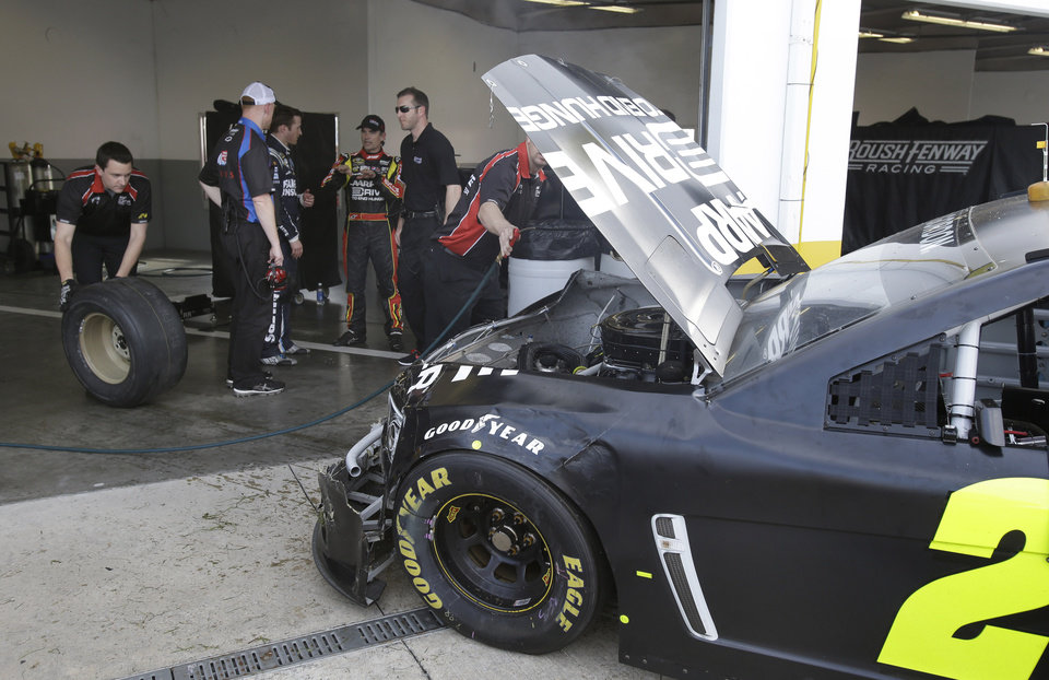 Jeff Gordon, back center, talks with Kasey Kahne and crew members as damage to his car is evaluated after he was involved in a crash during NASCAR auto race testing at Daytona International Speedway, Friday, Jan. 11, 2013, in Daytona Beach, Fla. (AP Photo/John Raoux)