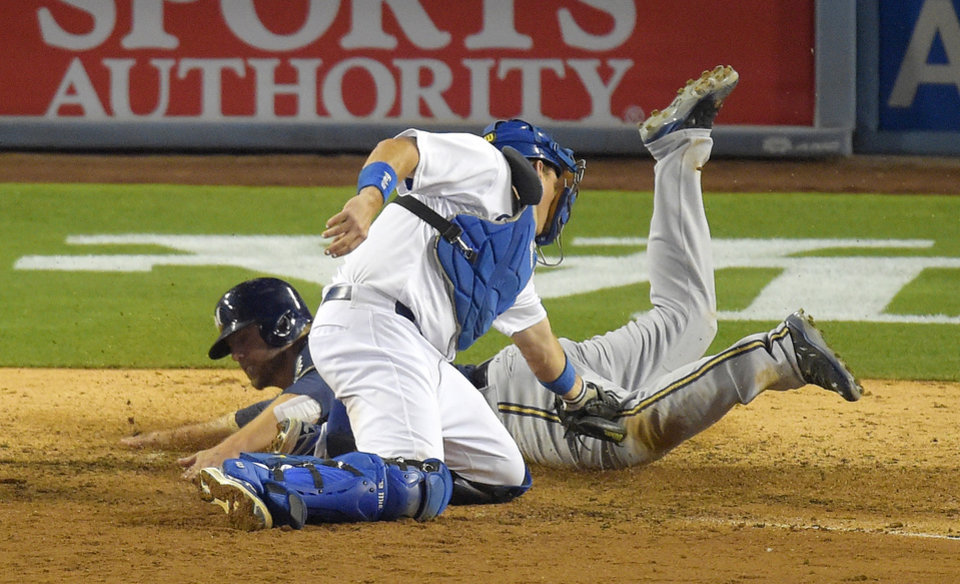 Photo - Milwaukee Brewers' Mark Reynolds, rear, scores on a double by Lyle Overbay as Los Angeles Dodgers catcher A.J. Ellis makes a late tag during the eighth inning of a baseball game, Friday, Aug. 15, 2014, in Los Angeles. (AP Photo/Mark J. Terrill)