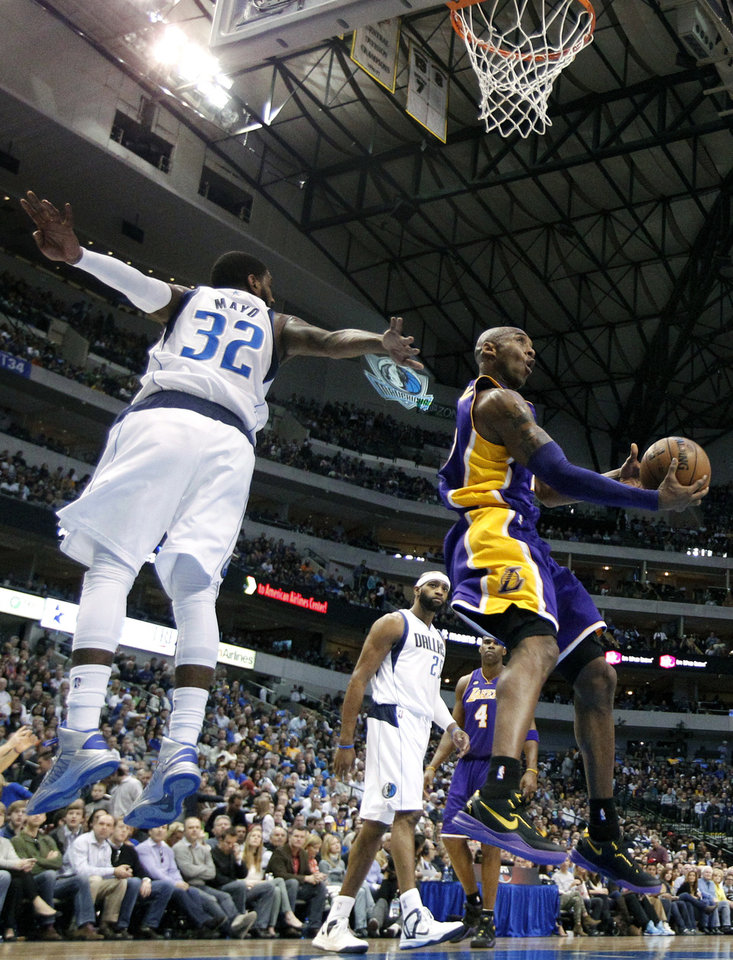 Dallas Mavericks' O.J. Mayo (32) defends as Los Angeles Lakers' Kobe Bryant goes up for a reverse layup score in the first half of an NBA basketball game Sunday, Feb. 24, 2013, in Dallas. (AP Photo/Tony Gutierrez)