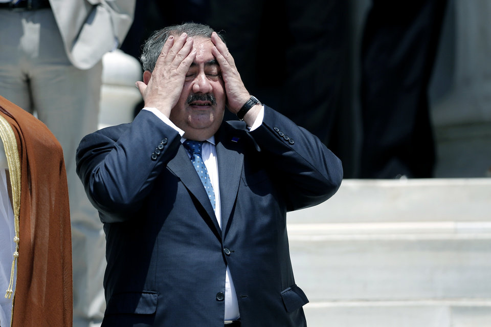 Photo - Iraqi Foreign Minister Hoshyar Zebari reacts to the heat before a group photo during an EU-Arab league Foreign Ministers summit in Athens, on Wednesday, June 11, 2014. The fall of the major northern Iraqi city of Mosul to insurgents must push the country's leaders to work together and deal with the
