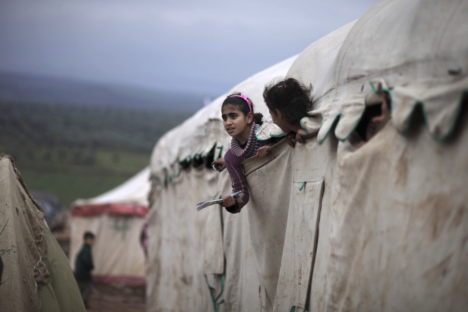 In this Monday, Dec. 10, 2012 photo, Syrian girls who fled their homes with their families peek out of their makeshift school at a camp for displaced Syrians in the village of Atmeh, Syria. This tent camp sheltering some of the hundreds of thousands of Syrians uprooted by the country\'s brutal civil war has lost the race against winter: the ground under white tents is soaked in mud, rain water seeps into thin mattresses and volunteer doctors routinely run out of medicine for coughing, runny-nosed children. (AP Photo/Muhammed Muheisen) ORG XMIT: XMM514