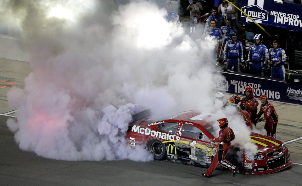 Photo - Jamie McMurray is helped from his car during a NASCAR Sprint Cup Series auto race at Kansas Speedway in Kansas City, Kan., Saturday, May 10, 2014. (AP Photo/Charlie Riedel)