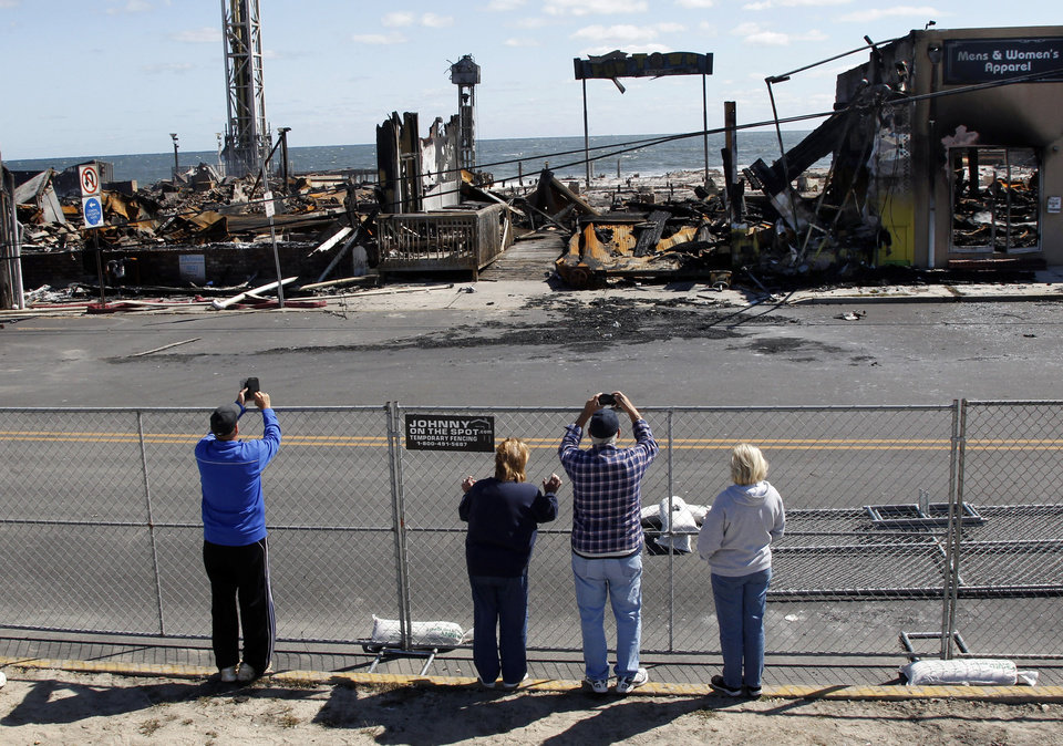 Photo - People take photographs of the charred rubble in Seaside Park, N.J., Tuesday, Sept. 17, 2013, after a fire last Thursday that started near a frozen custard stand in Seaside Park,  quickly spread north into neighboring Seaside Heights. More than 50 businesses in the two towns were destroyed. The massive boardwalk fire in New Jersey began accidentally, the result of an electrical problem, an official briefed on the investigation said Tuesday. (AP Photo/Mel Evans)
