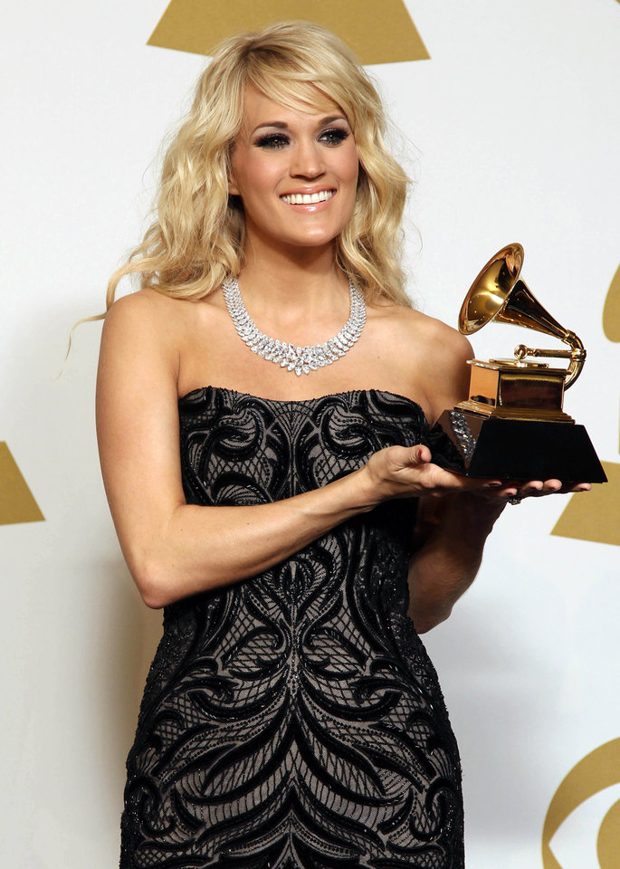 "Carrie Underwood poses backstage with the award for best country solo performance for ""Blown Away"" at the 55th annual Grammy Awards on Sunday, Feb. 10, 2013, in Los Angeles. (Photo by Matt Sayles/Invision/AP) ORG XMIT: CASH199"