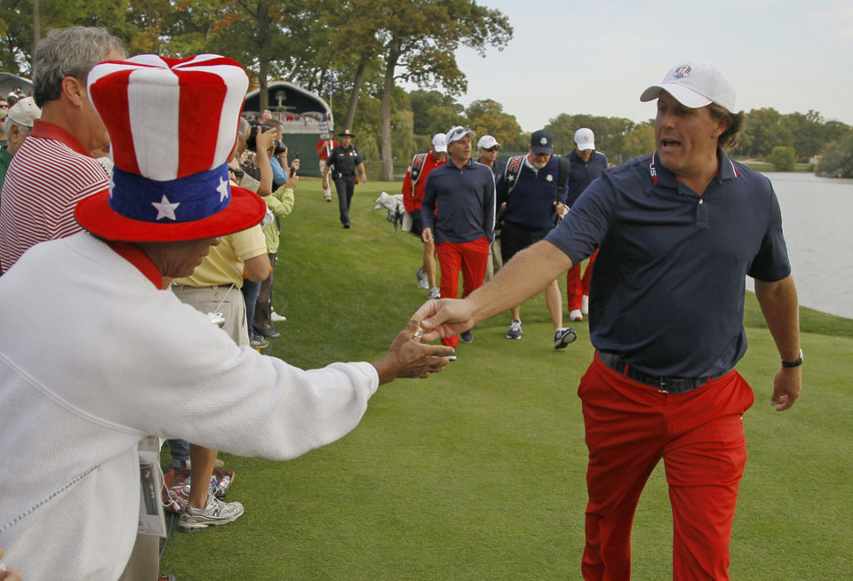 Photo -   USA's Phil Mickelson hands fan Richard Atkins a pin after teeing off on the second hole at the Ryder Cup PGA golf tournament Wednesday, Sept. 26, 2012, at the Medinah Country Club in Medinah, Ill. (AP Photo/Charles Rex Arbogast)